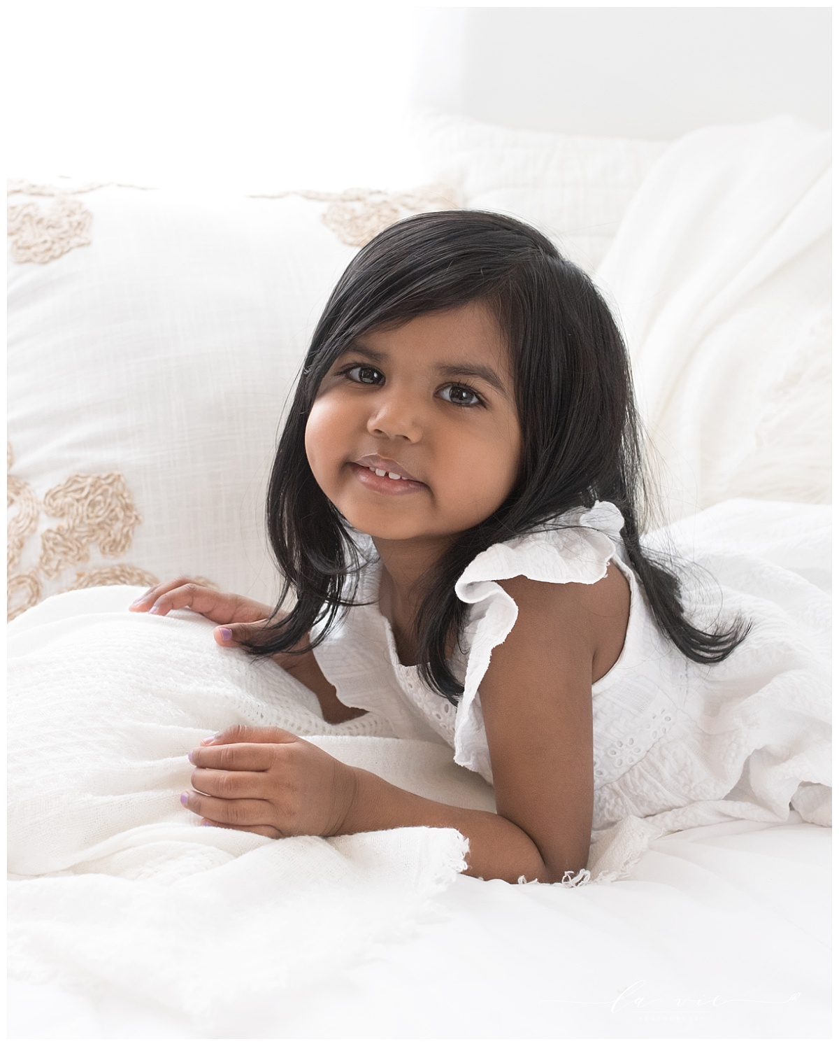 Closeup portrait of toddler girl with dark hair on white bed