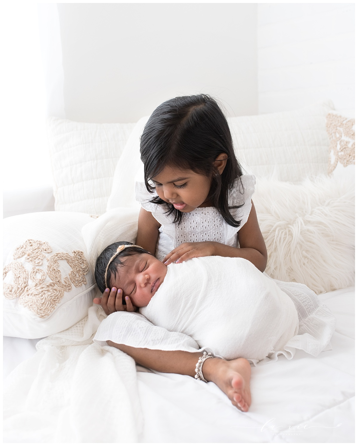 Big sister holding her newborn baby sister on white bed