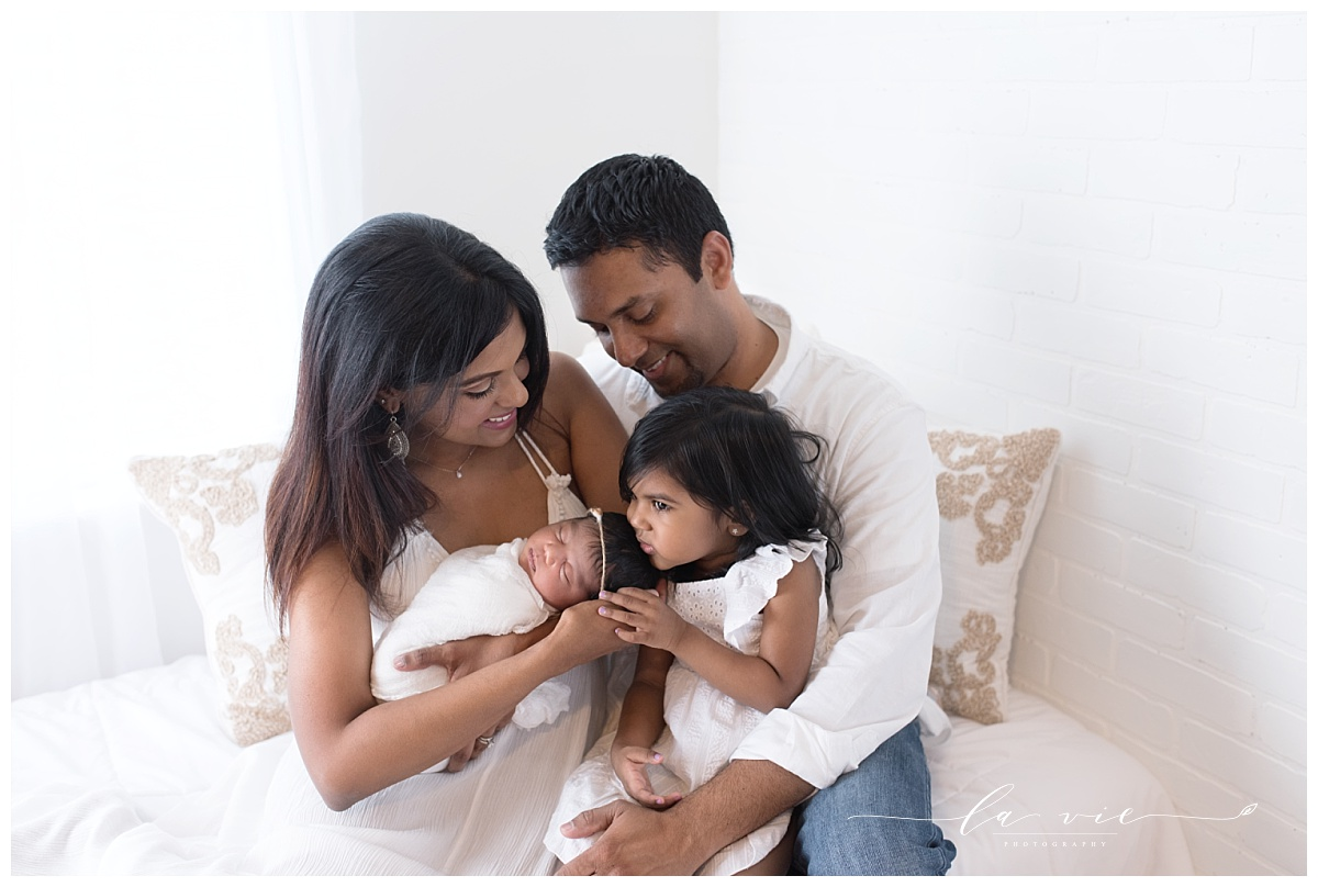 Relaxed family pose on white bed with newborn girl and big sister