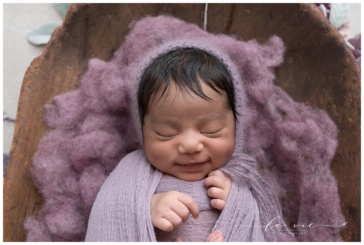 Newborn baby girl smiles lying on purple wool in a wood bowl