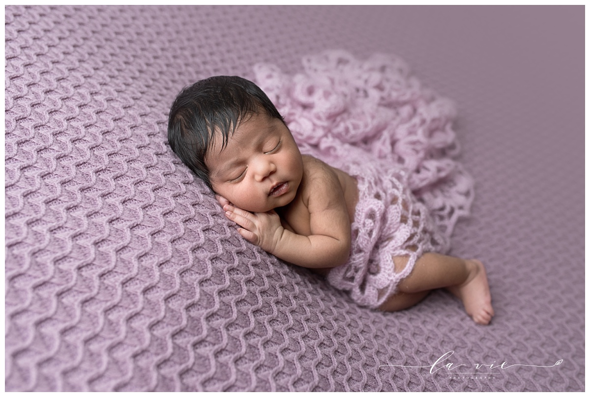 Newborn baby girl laying on her side wrapped in lavender