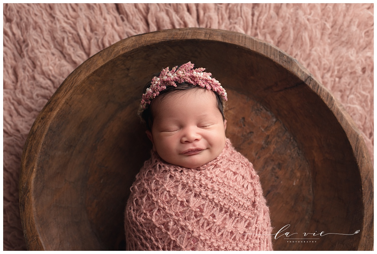 Closeup of newborn girl wrapped in pink and posed in wood bowl