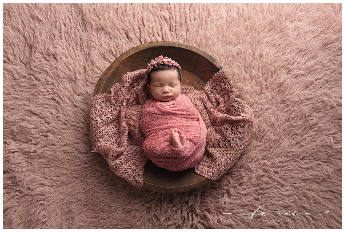 newborn girl posed on wood bowl and pink rug