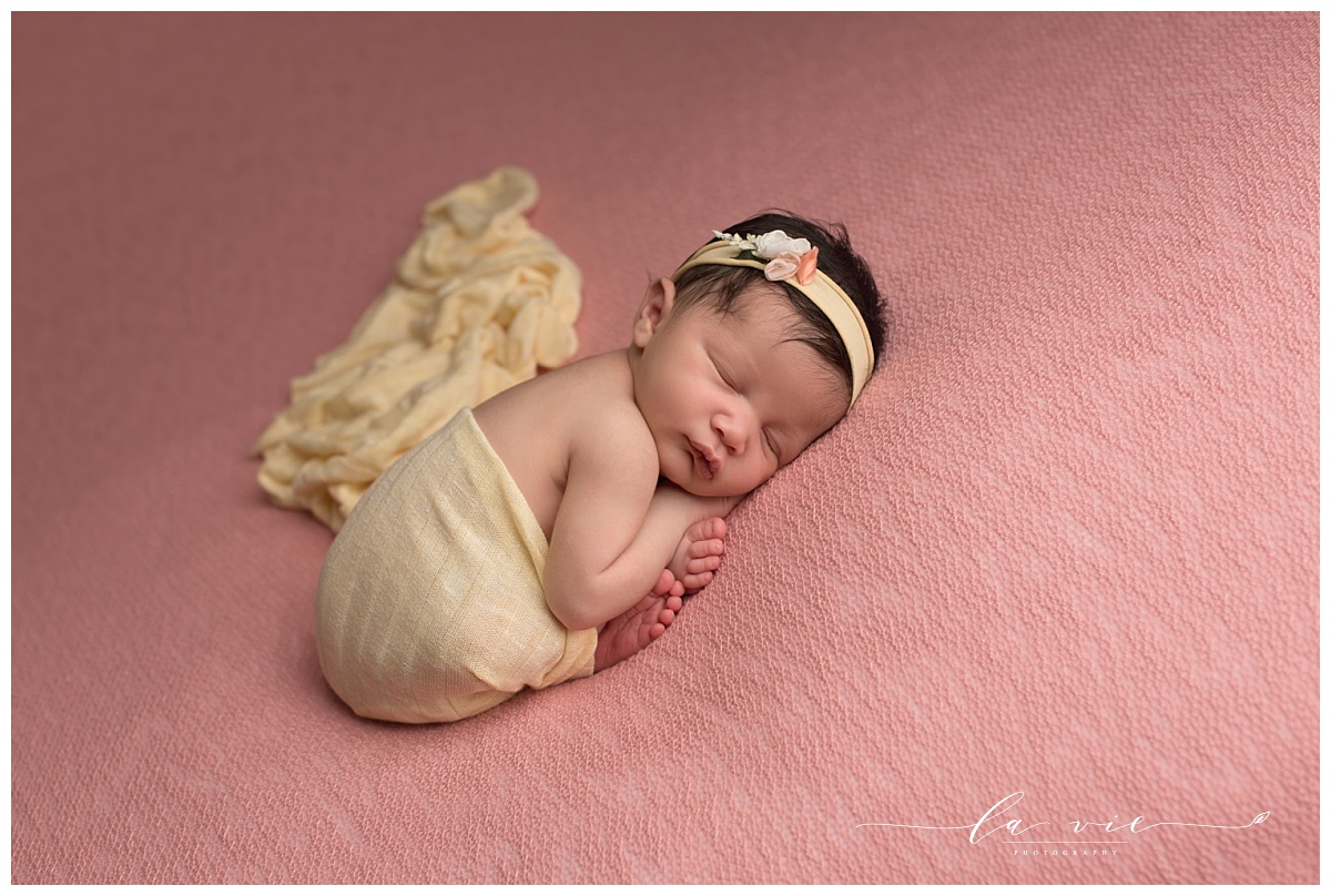 newborn baby girl on pink background with yellow wrap