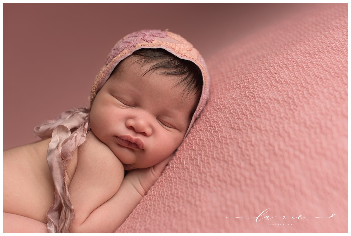 closeup of newborn baby girl in pink bonnet