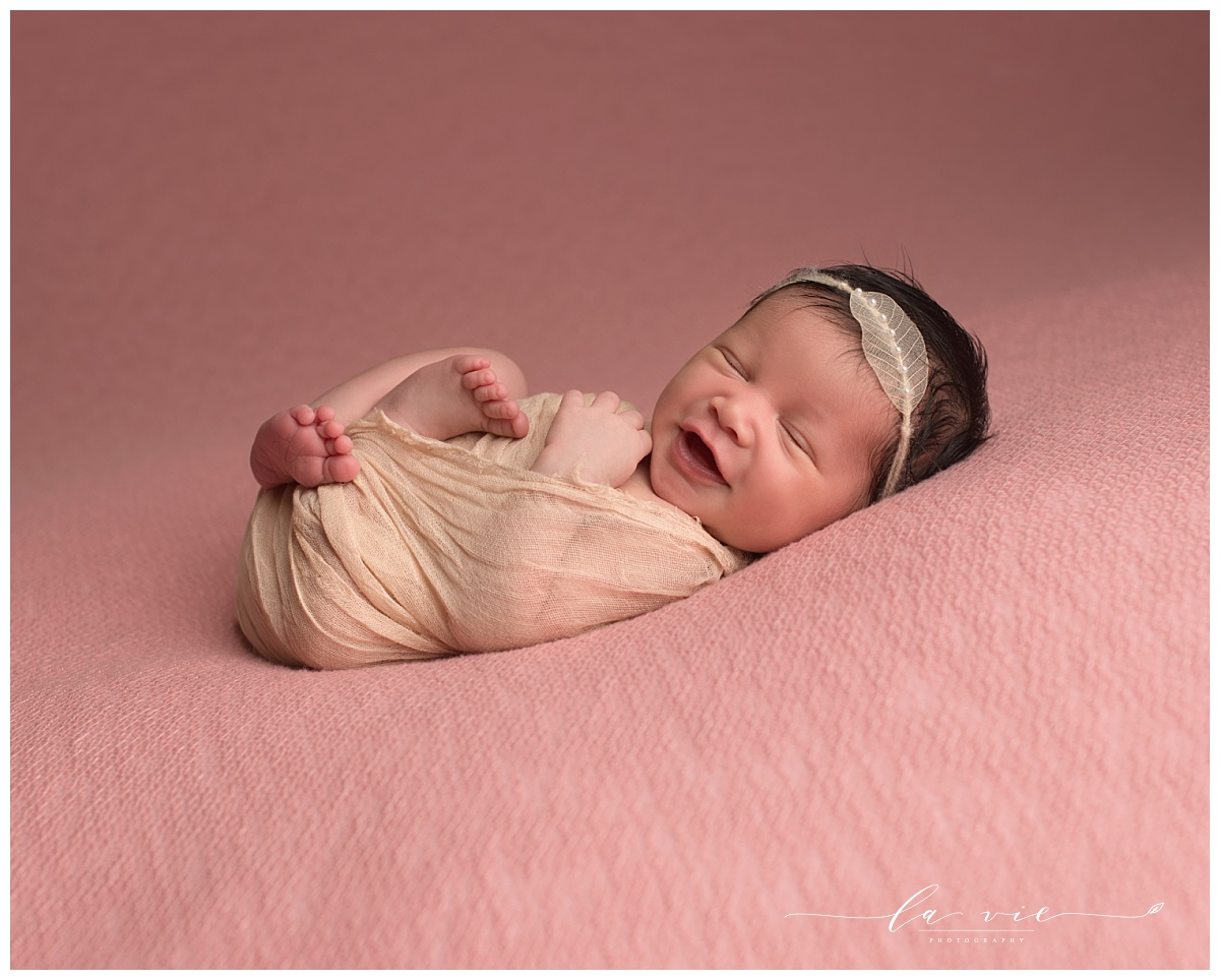newborn baby girl smiling big