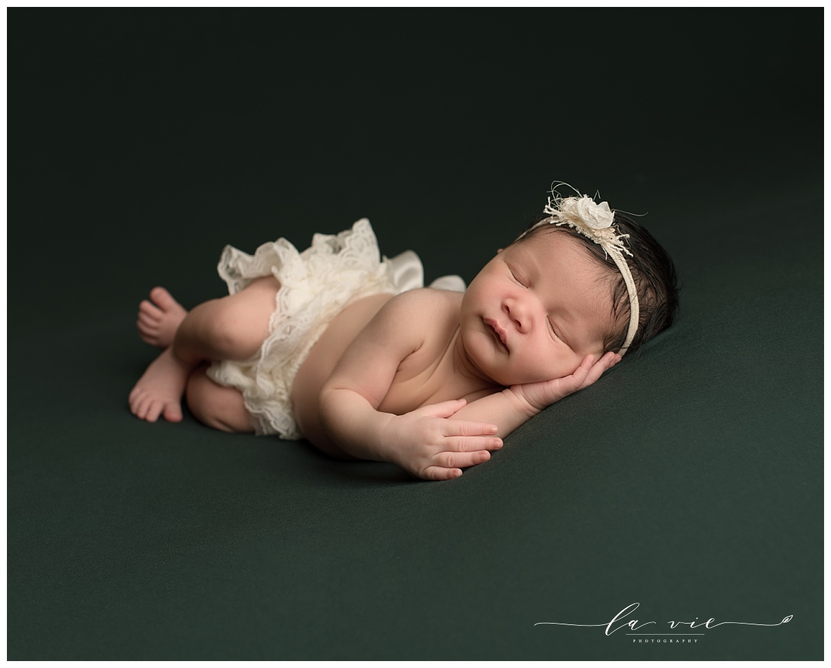 newborn girl sleeping on dark green background