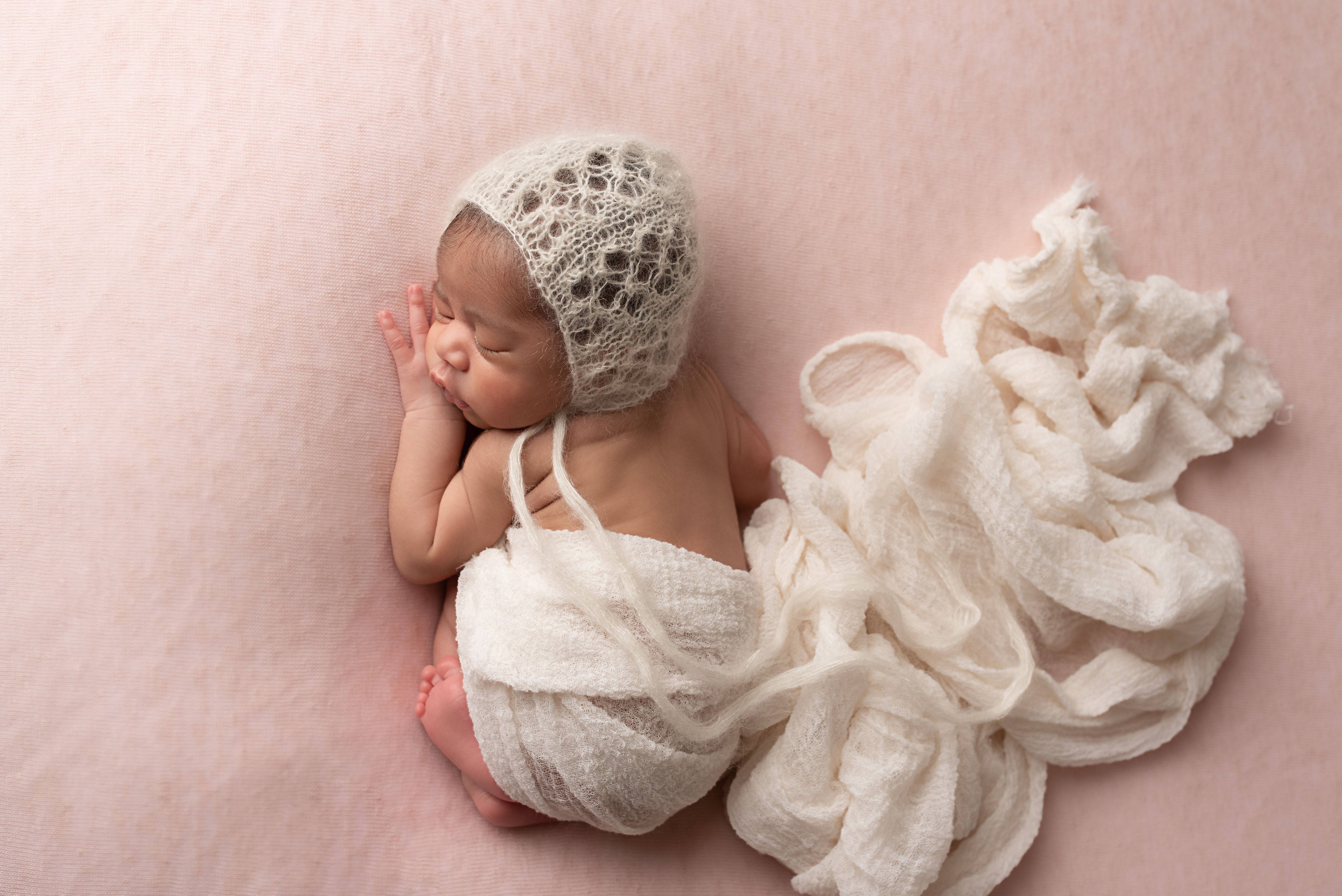 Newborn girl photographed on pink