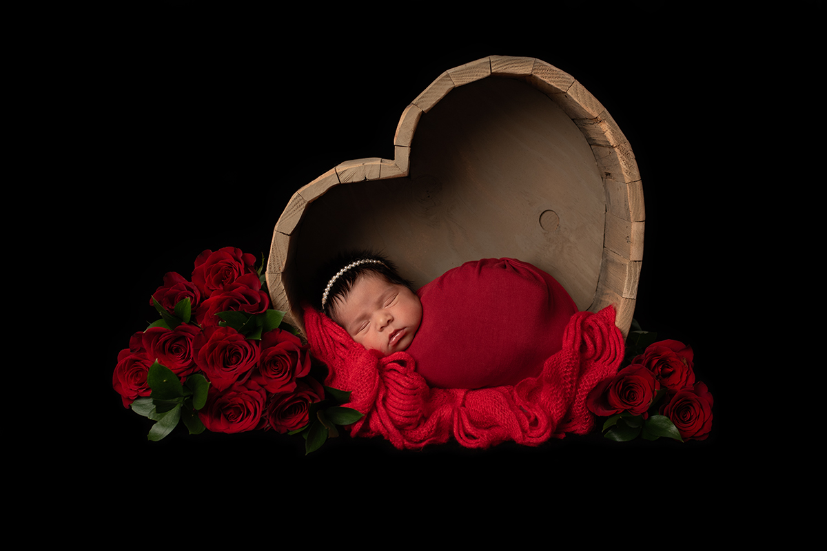 Newborn portrait with hearts and red roses